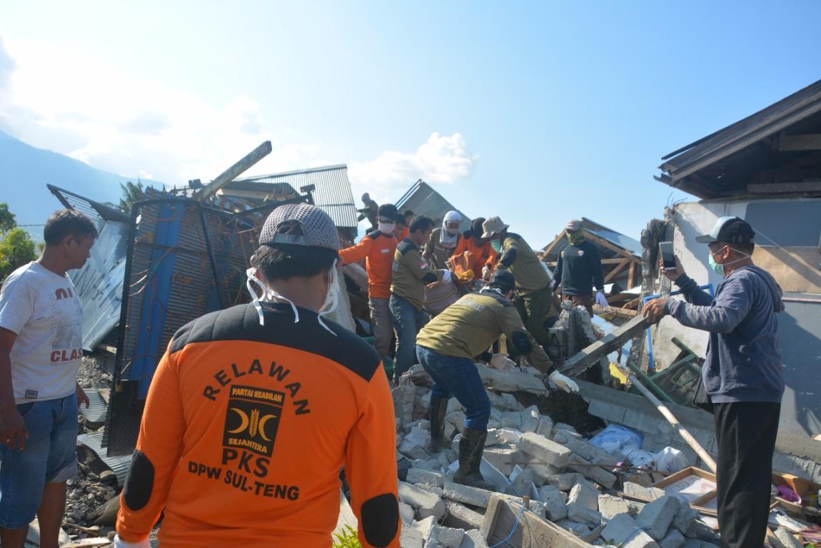 Relawan PKS sedang membantu mengevakuasi korban yang tertimbun reruntuhan bangunan